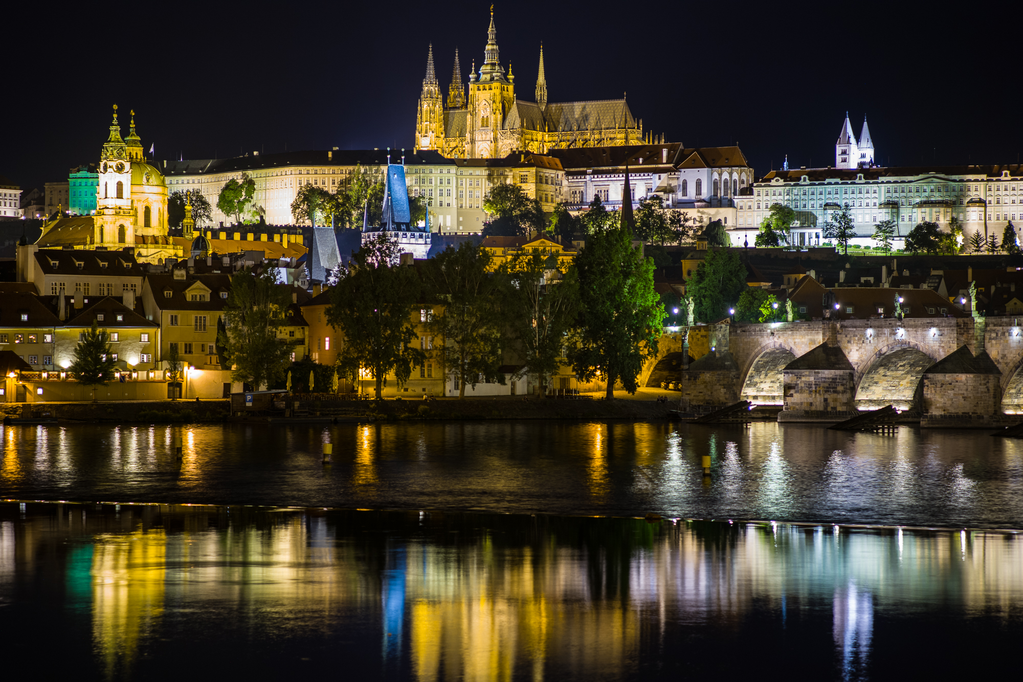 Prague Castle and the Charles Bridge at night as seen from the banks of the Vltava River
