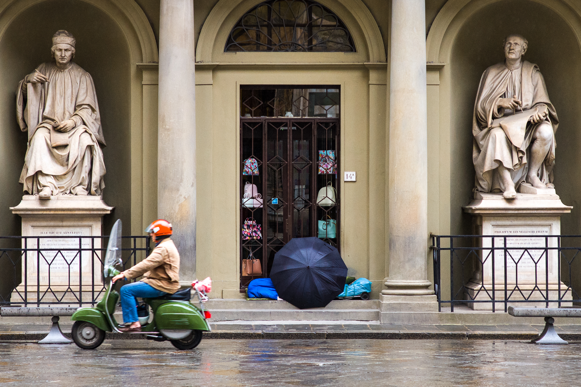 Vespa riding past a homeless man in Florence