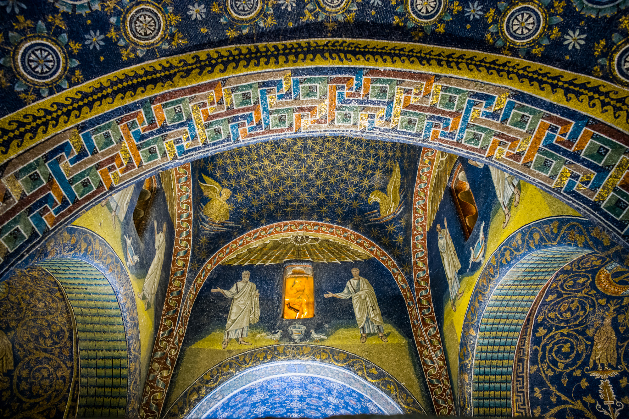The Mosaics of the Mausoleum of Galla Placidia. The sun's light shines through windows of cut stone.