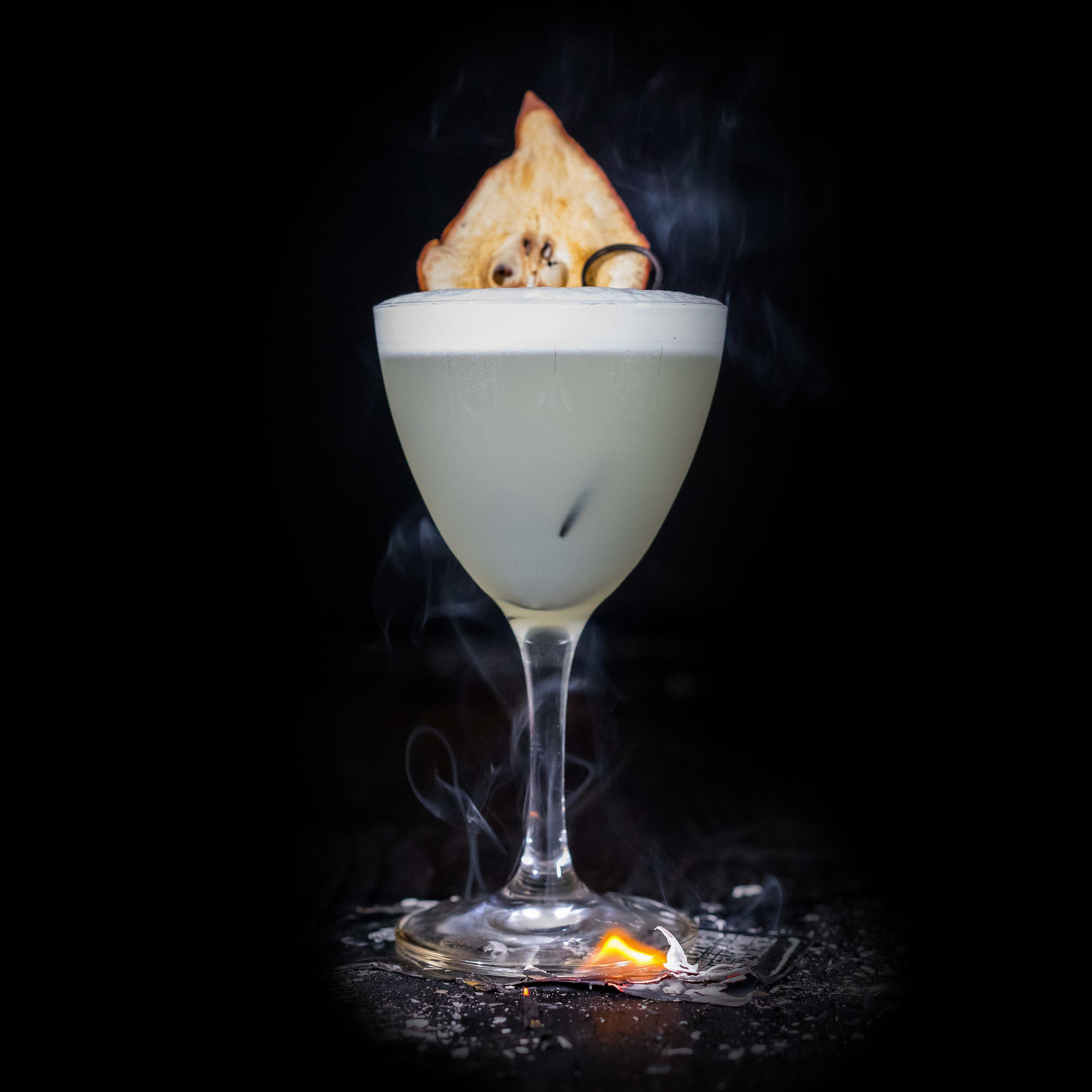 SMOKED PEAR SOUR  INGREDIENTS  - 1.5 oz. El Silencio Espadin - .75 oz. St. George Spiced Pear Liqueur - .75 oz. Simple Syrup - .75 oz. Fresh Lime Juice - Egg White  METHOD  Dry Shake In a mixing vessel,  Shake with ice & Strain Pear Feather - Cocktail Coupe
