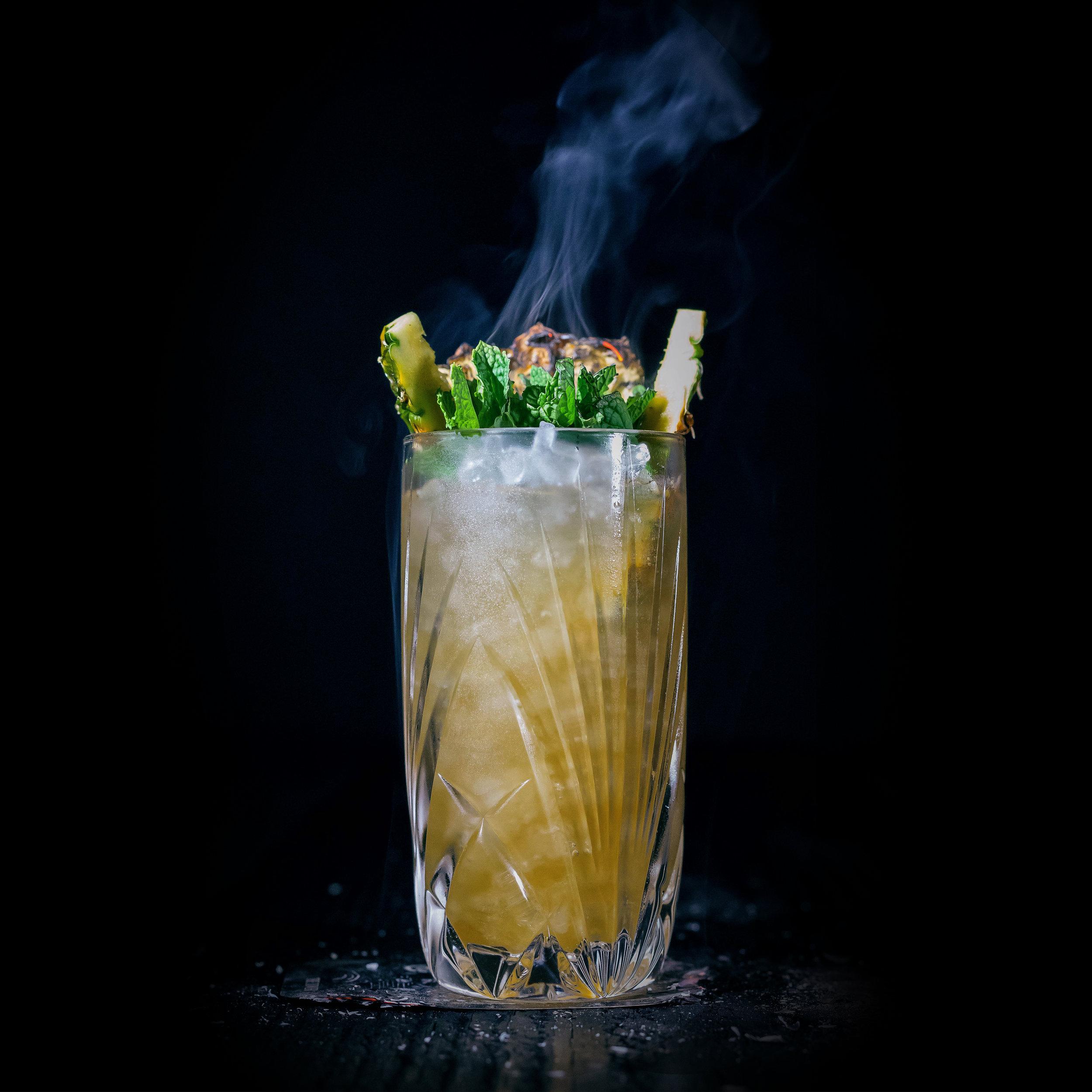 ZAPOTEC ZOMBIE  INGREDIENTS  - 2 oz. El Silencio Espadin - .5 oz. Dos Maderos 5x5 Rum - .5 oz. Hamilton 151 Rum - .75 oz. Passion Fruit Syrup - .75 oz. Demerara Syrup - .75 oz. Lime Juice - .75 oz. Lemon Juice - .75 oz. Pineapple Juice - Dash Angostura  METHOD  Shake & Pour Pineapple Leaves & Nutmeg - Pilsner Glass