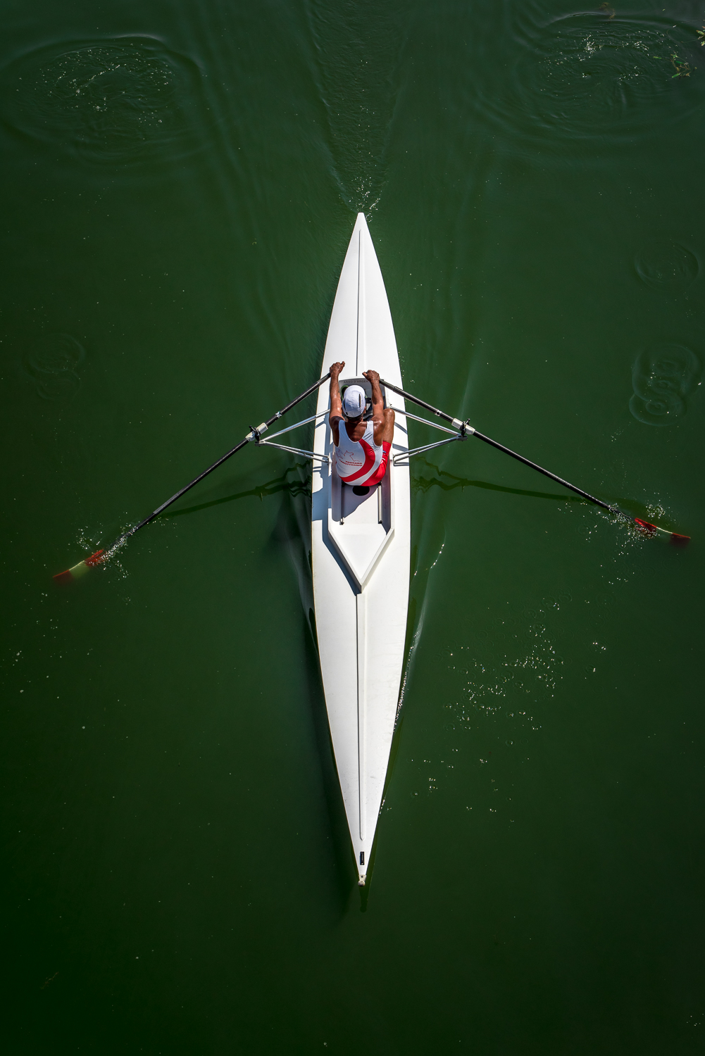 ©Ayash Basu. Looking straight on at eye level would not have captured the geometry of the kayak, I was standing on a bridge and waited for the kayak to pass below me to get this top-down shot.