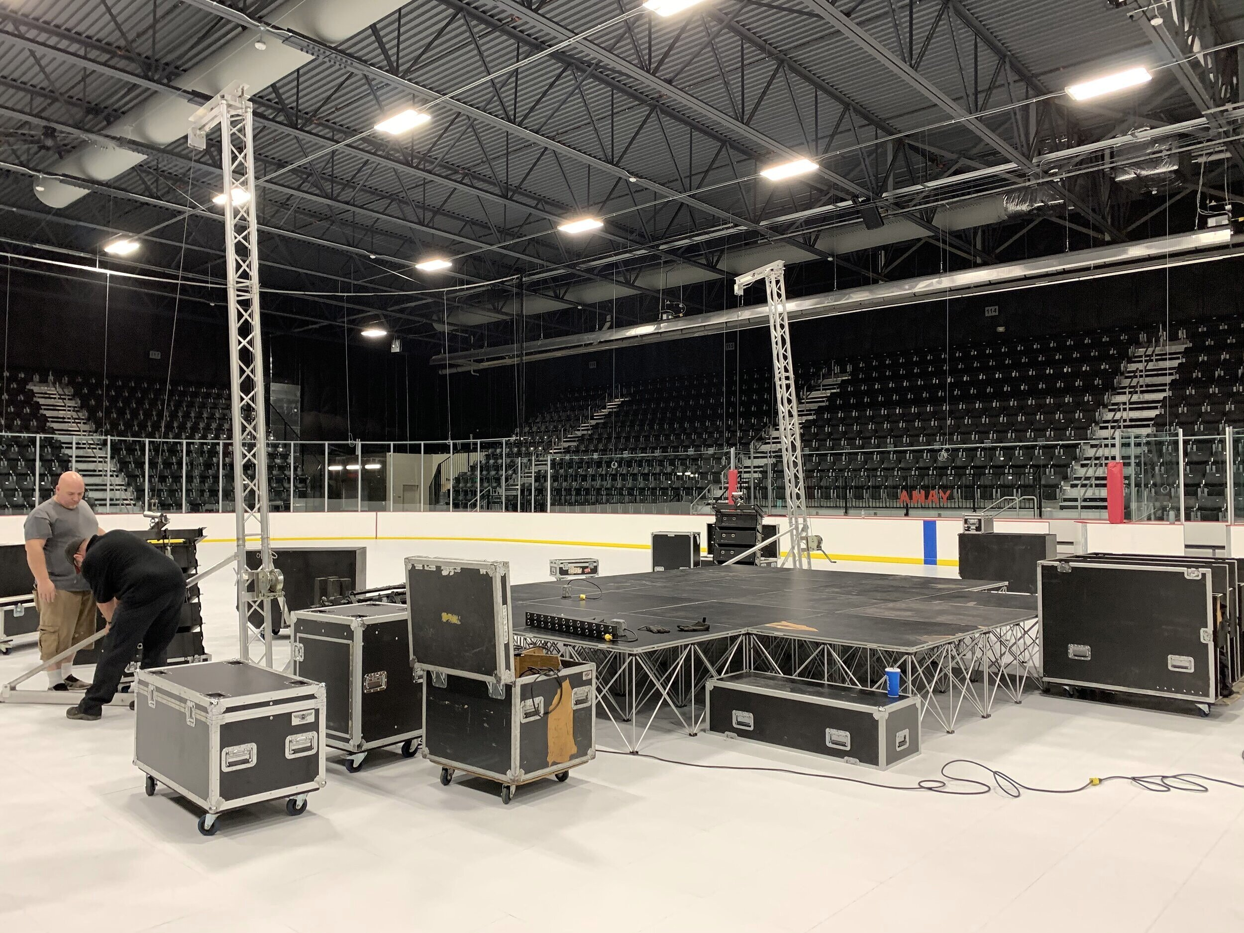 Build stages and load speaker towers onto the flooring.