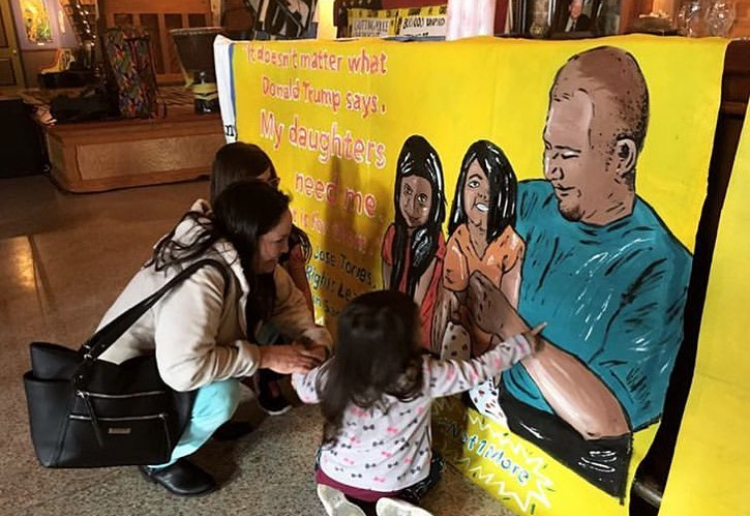 Collaborative banner work featuring family of local immigrant rights leader  Jose Torres . Photo by Chloe Sigal.