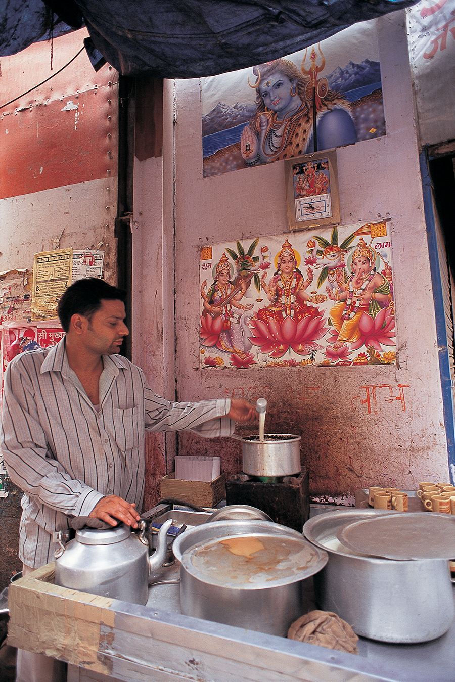 A tea stall in Chandni Chowk, Delhi. Shiva's three aspects—as the god of truth, creative energy, and darkness (as destroyer)—makes him a prominent figure in popular art, and his imagery pervades everyday life, thereby connecting earth life to a mythical one. Photo:Delhi, India