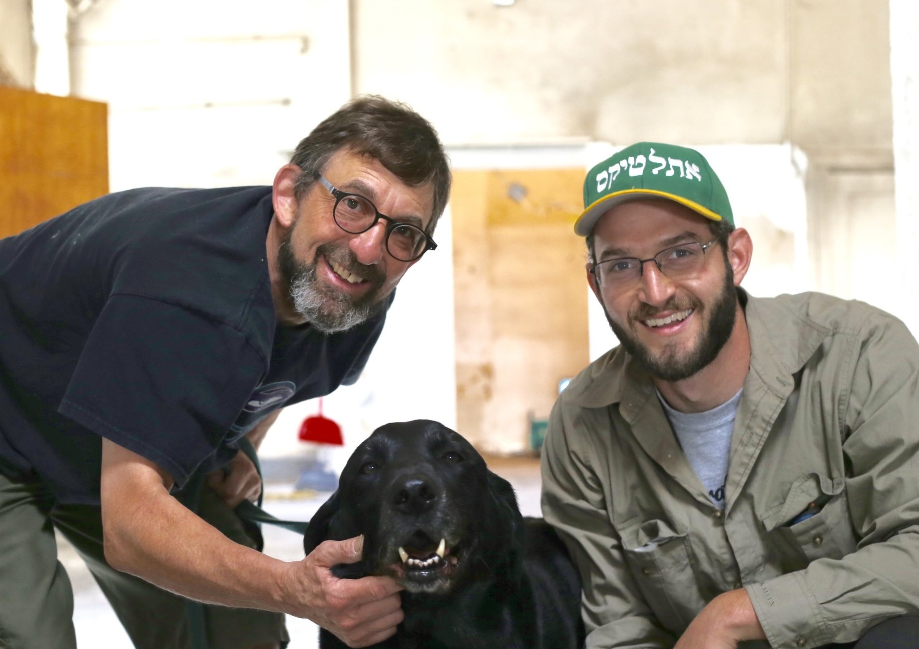 Former Grand Bakery owner, Bob Jaffe (left) with new owner, Sam Tobis (right), along with Mr. Moochie, the pup (center).