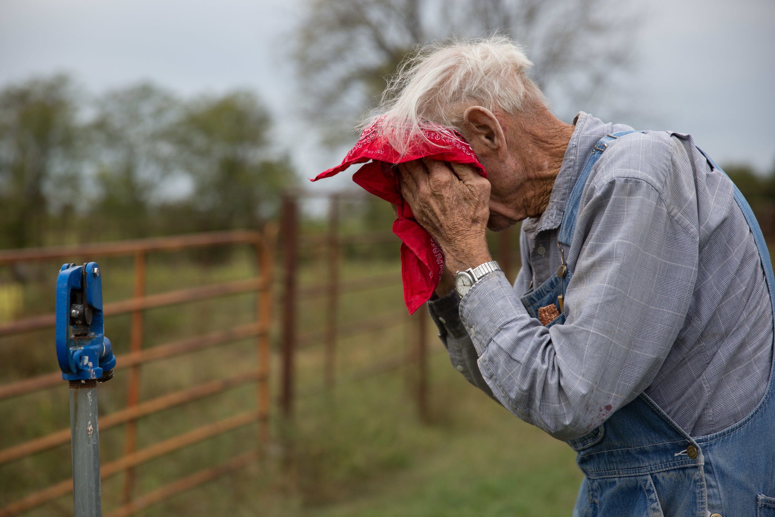 Carl takes a moment to clean his face after a dusty day of harvesting corn.