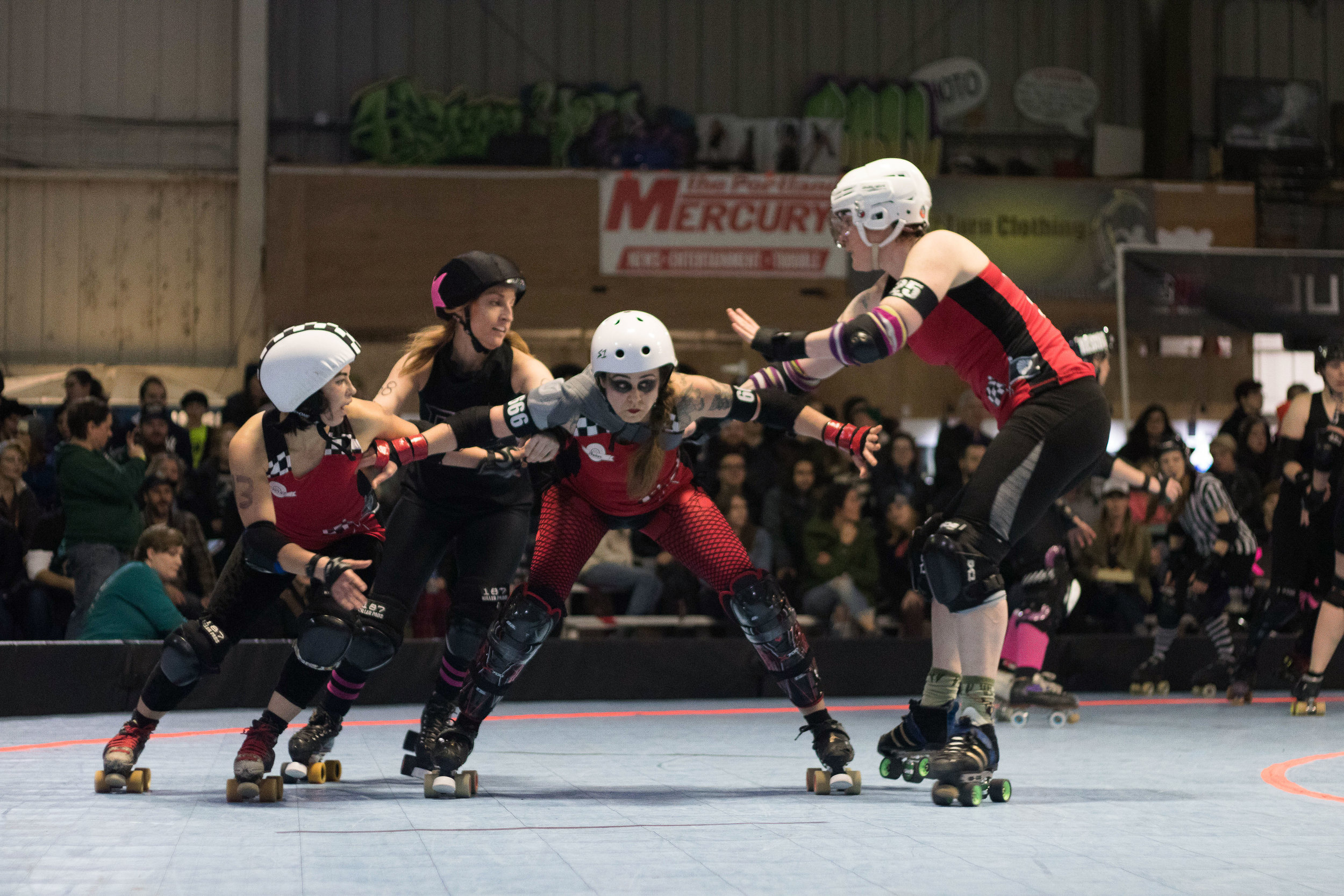 Smelter Skelter (center) and Break Neck Betties teammates block players from opposing team Guns N Rollers at Oaks Park in Portland, Ore., May 13, 2017. Guns N Rollers defeated the Break Neck Betties 226-222.