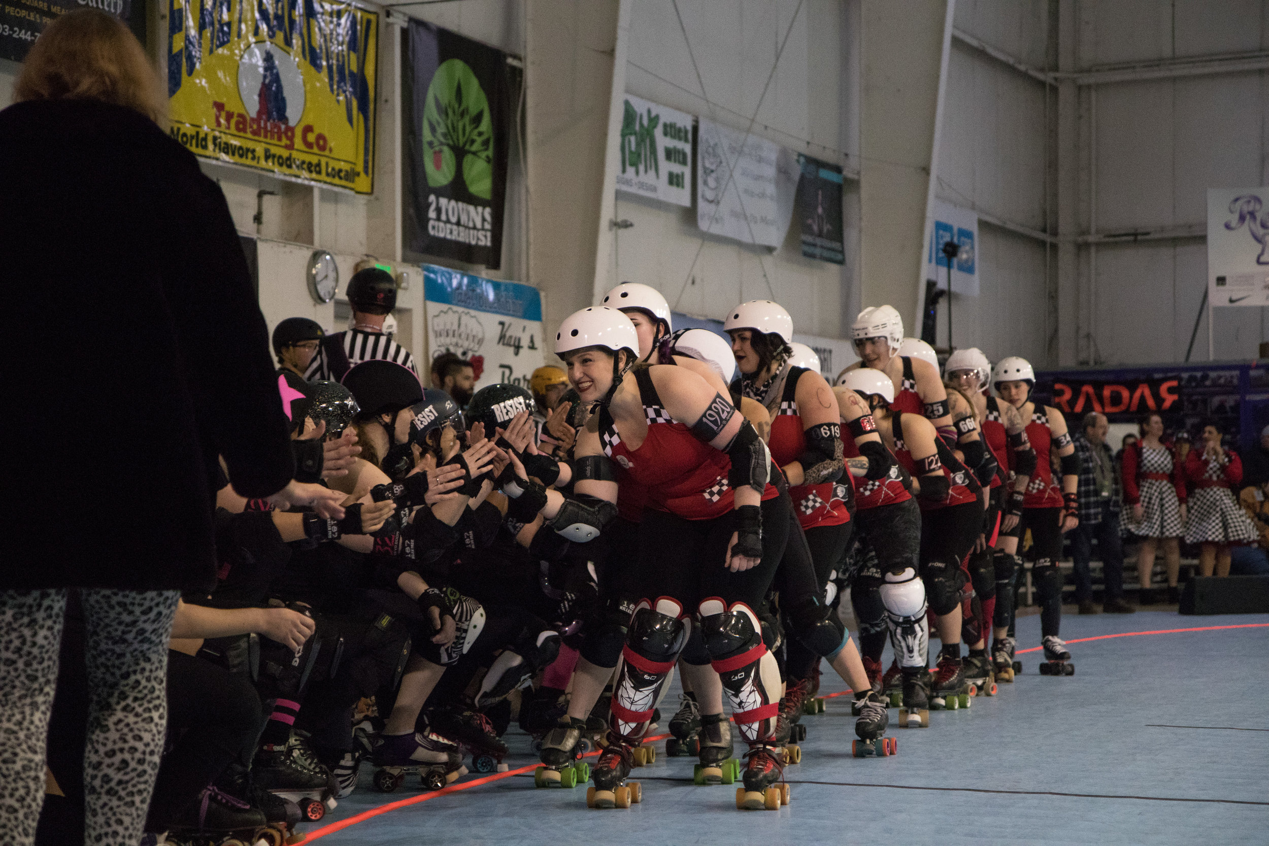 Susan B. Animosity (front) and the Betties shake hands with opponents Guns N Roses. Though they are intense rivals on the track, many have close friendships with players from teams across the league. Break Neck Betties hold the league record for the most championship wins in Rose City Rollers history.