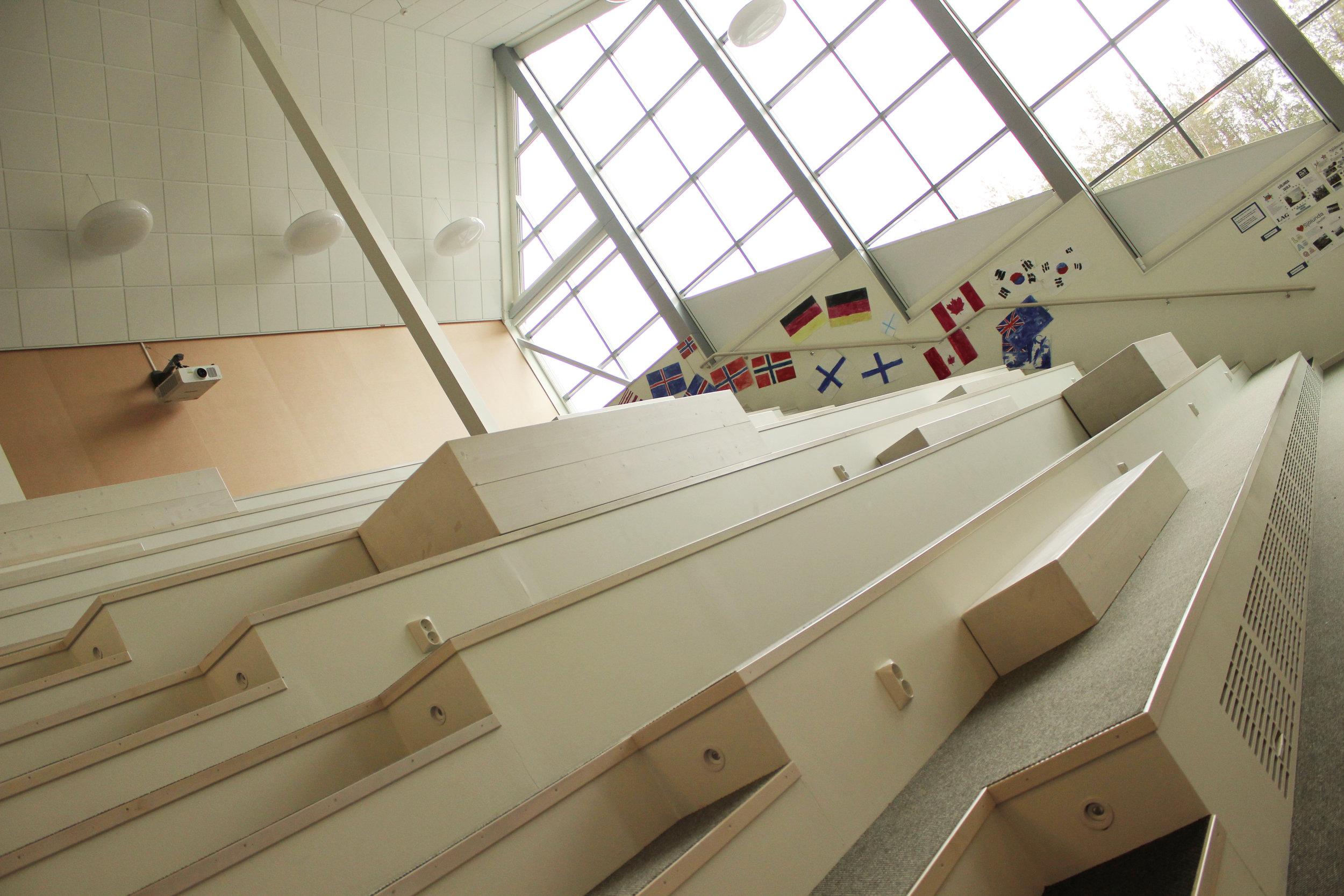 Sittplatserna är många även i den amfiteaterliknande aulan. På håll kan du skymta en av skolans få projektorer, en Panasonic PT-RZ970LW med linsen ETDLE350. Skärmar, å andra sidan, hittar man desto fler.