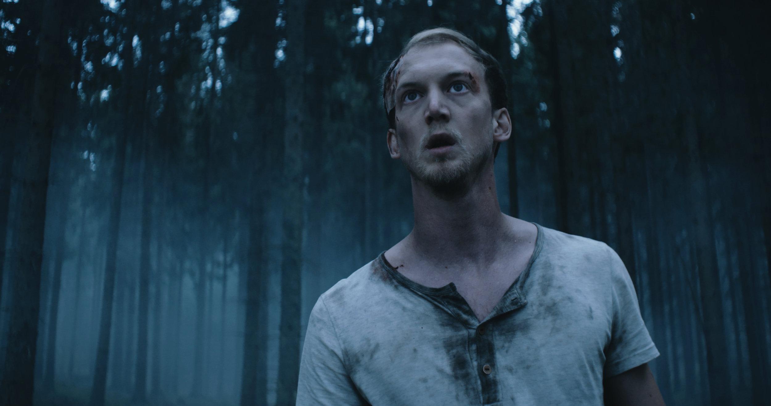 Katastrofen är ett faktum. Alex, spelad av Christoffer Nordenrot, spänner blicken i något med hjärtat i halsgropen i utkanten av skogsparti.