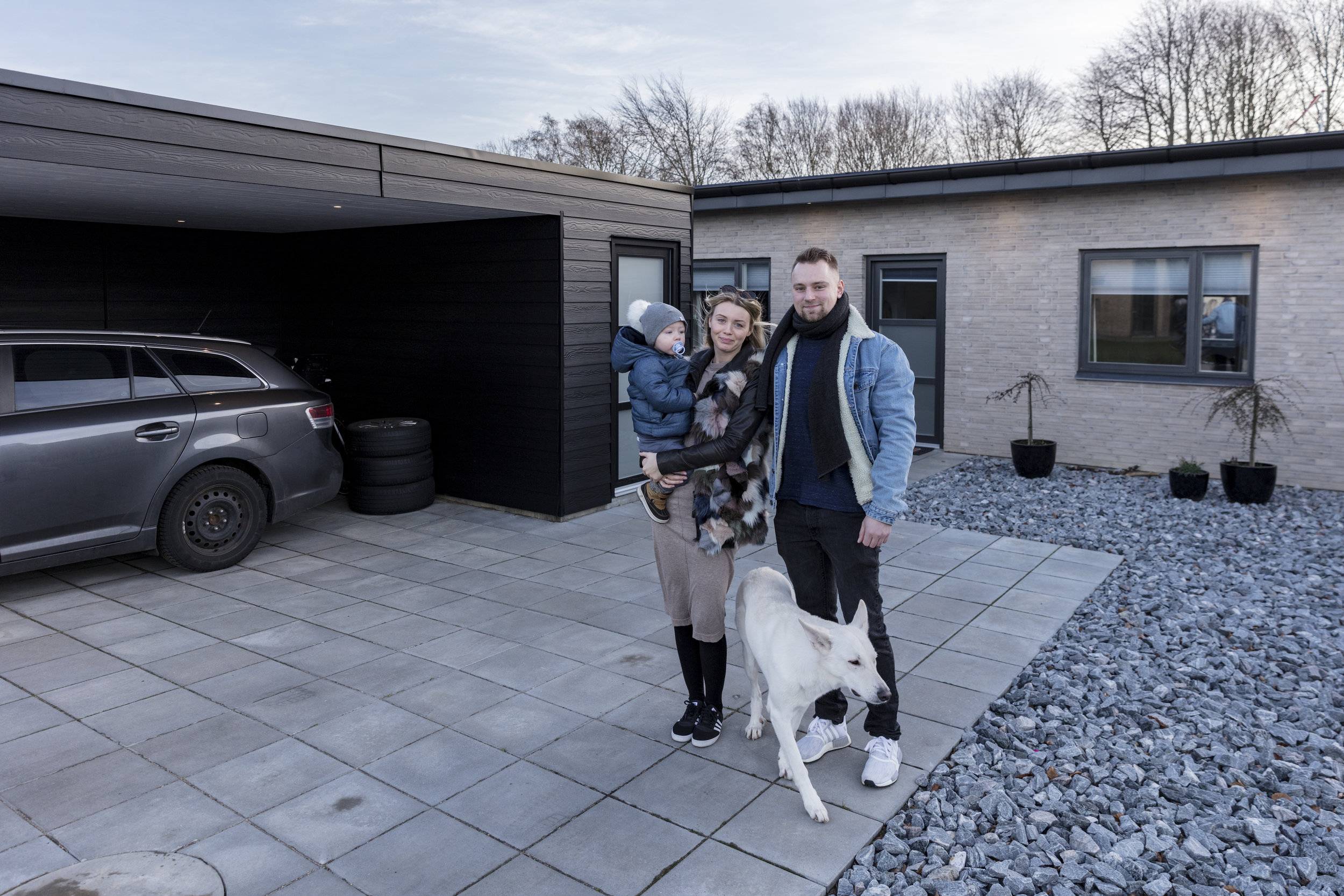 Anne & Tobias foran deres nye rækkehus sammen med sønnen Karl og hunden Bellis.