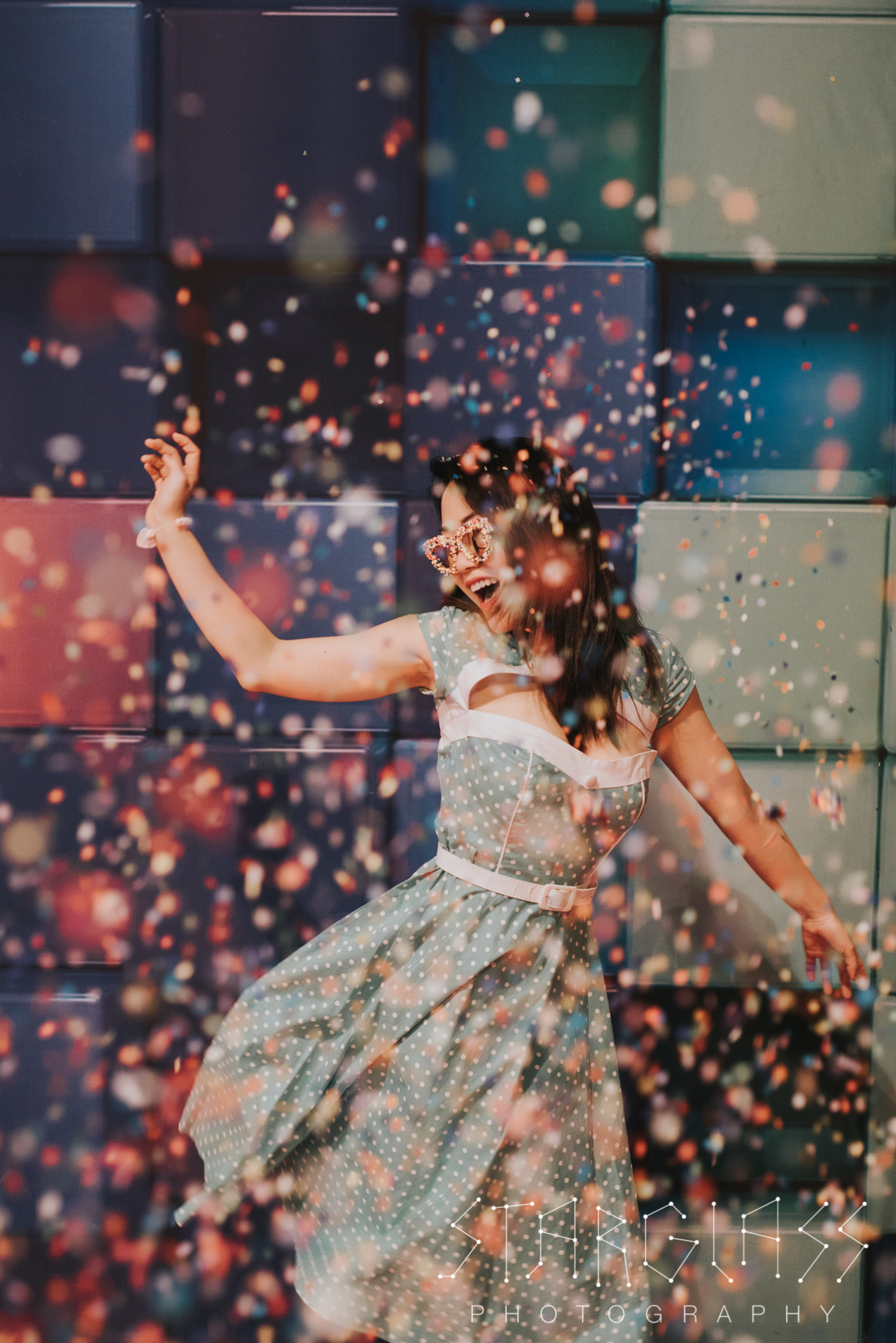 Portrait of a woman in a retro dress posing in a rainbow explosion of confetti.