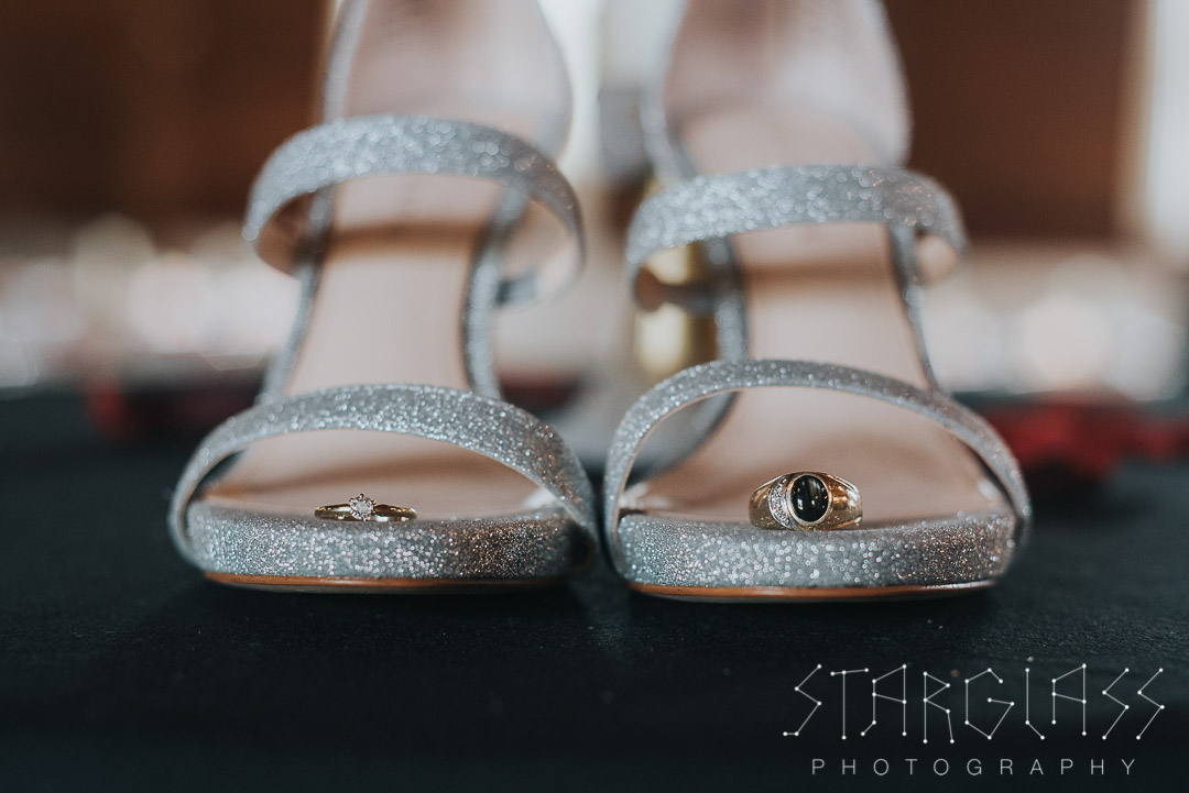 Photo of silver bride shoes and wedding rings.