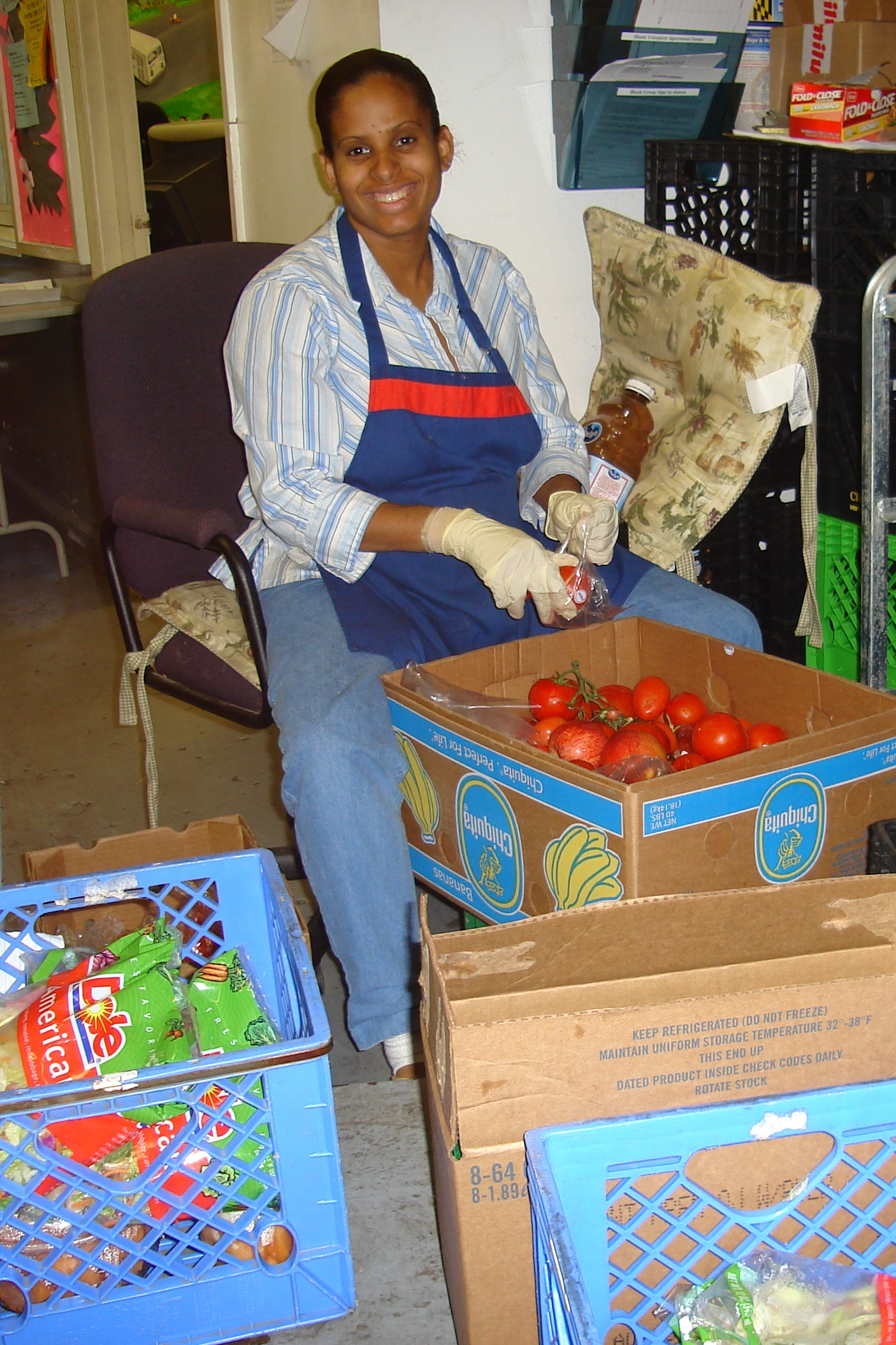 - A community member sorts produce at a local food center.