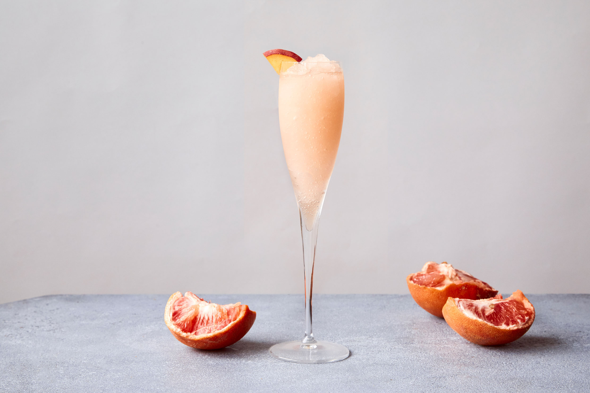 A frozen Bellini in a glass with fresh blood oranges around it.