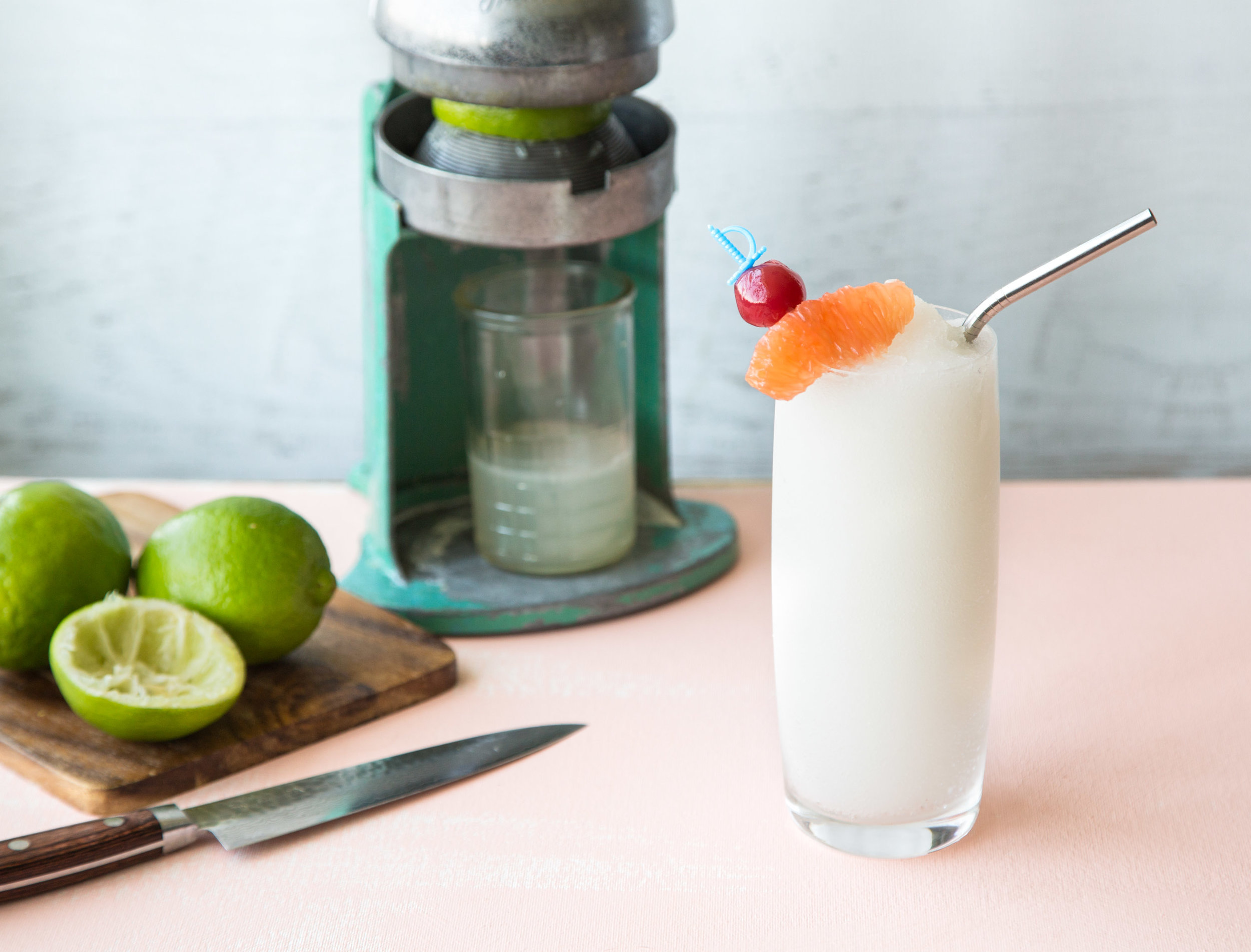 Frozen Daiquiri on a table next to a cutting board and juicer.