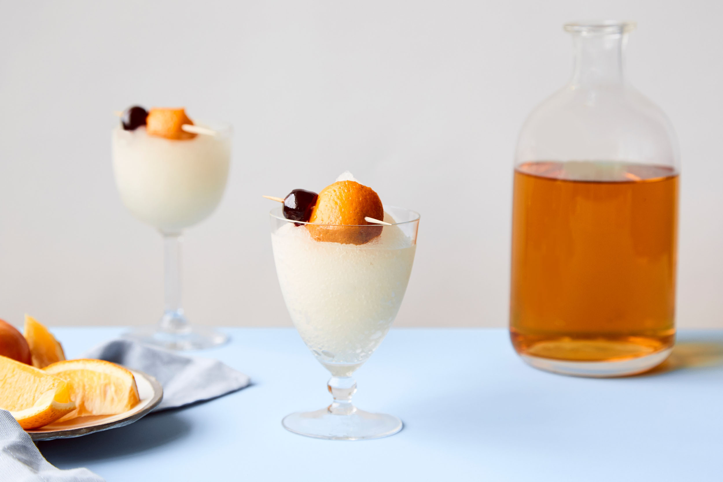 Frozen French 75 drink in a cup with fresh fruit.