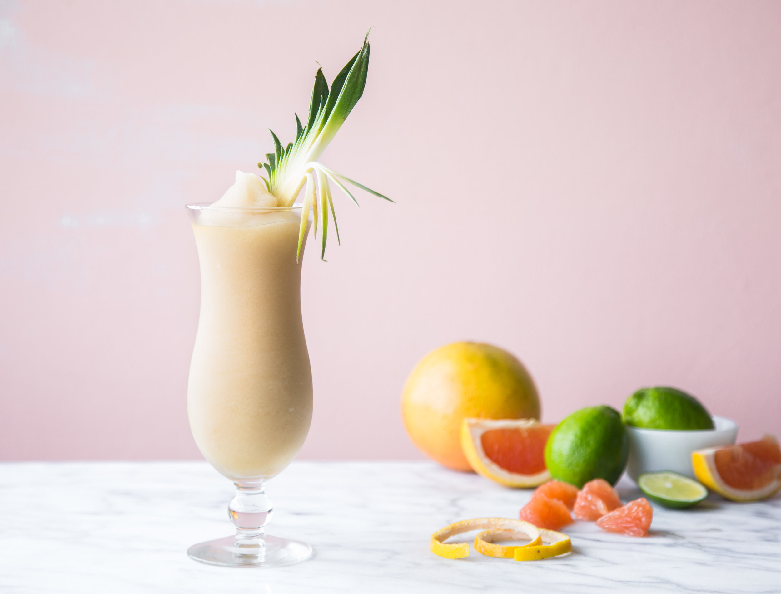 Ginger colada cocktail in a glass with fresh fruit.