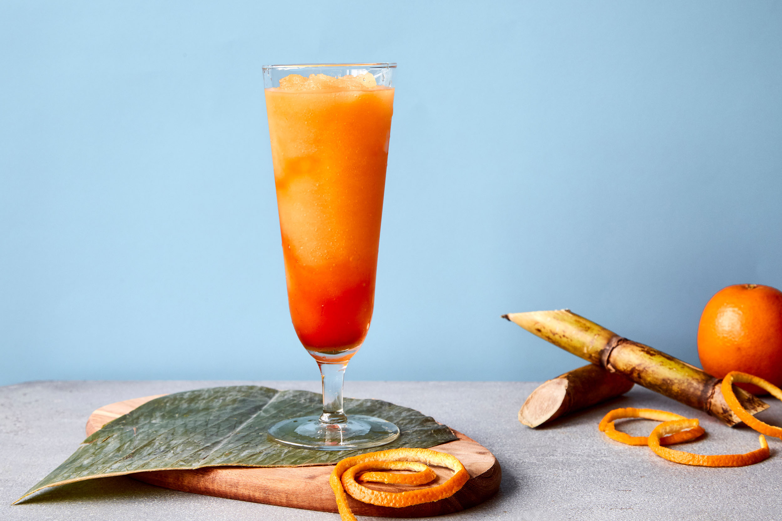 Frozen hurricane cocktail with an orange peel.