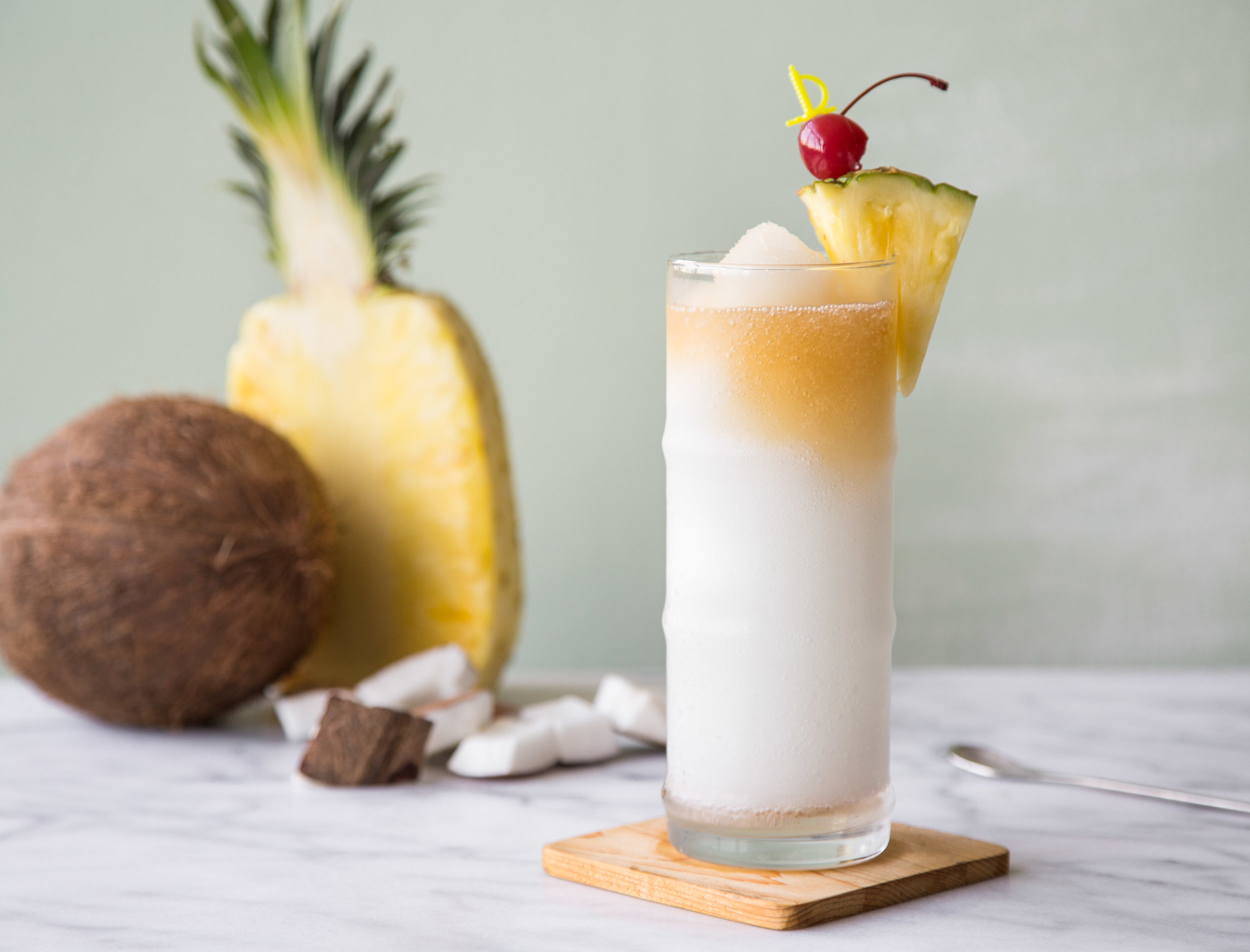 Pina Colada recipe in a glass with fresh pineapple.