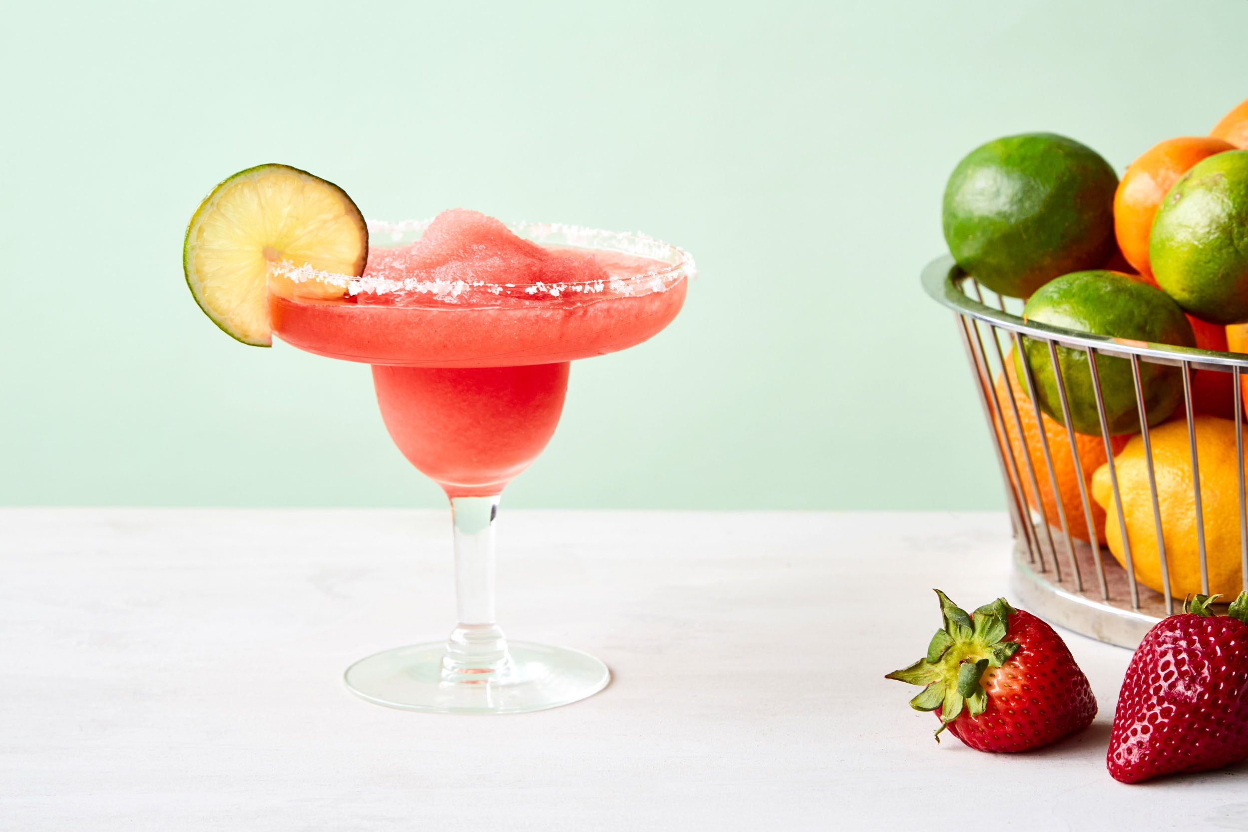 Frozen Strawberry Margarita in a glass with a lime.
