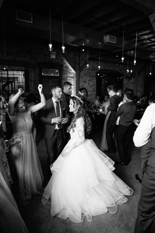 Bride dancing with wedding guests at Archeo Distillery District Toronto