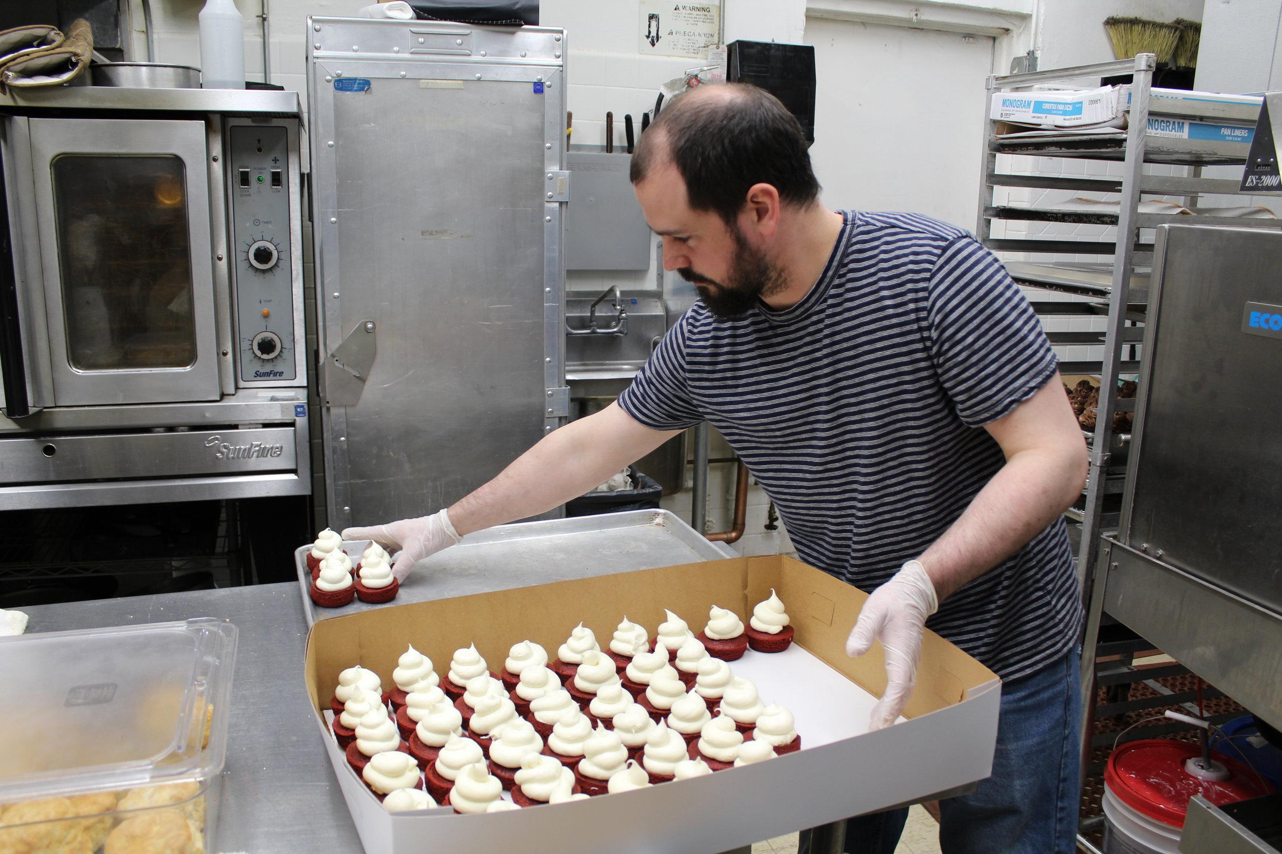 Owner Tim Benedict preparing cupcakes for donation
