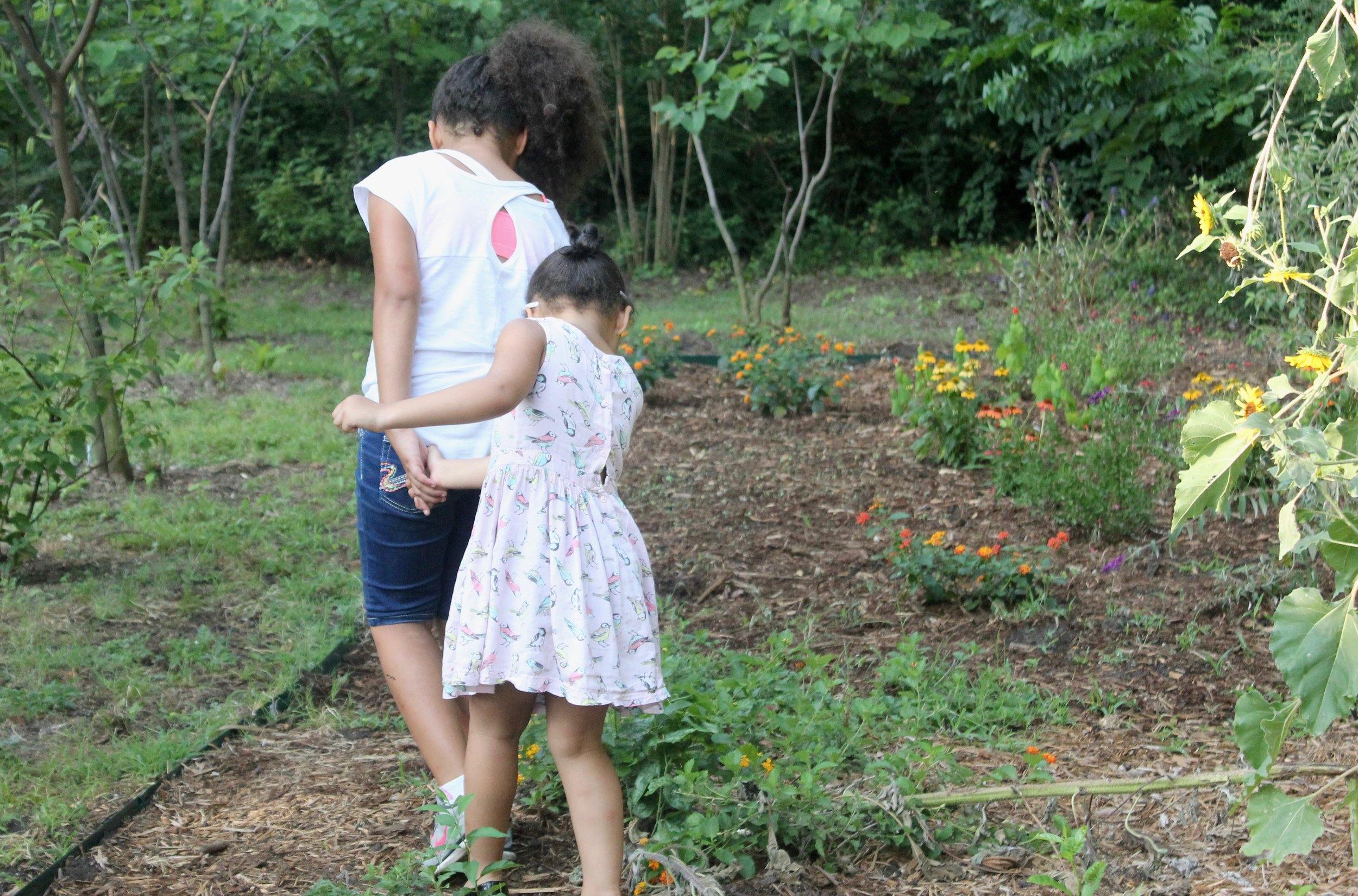 Two girls who live at The Wheeler House explore the Butterfly Garden