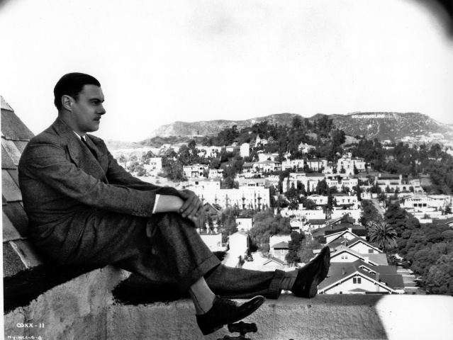 "Colin Clive, the original Dr. Frankenstein, poses on the rooftop of Hollywood Tower.  In the background you can see the Hollywood sign which originally read ""Hollywoodland."""