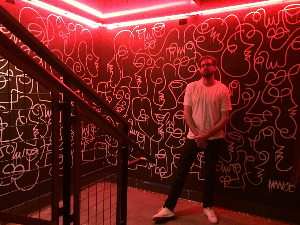 Matioc with his painting at Lucille. Photo courtesy of the artist.