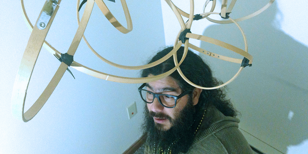 Victor Castro, with a hanging sculpture made of embroidery hooks, in his West Side studio. Photo by Scott Gordon.