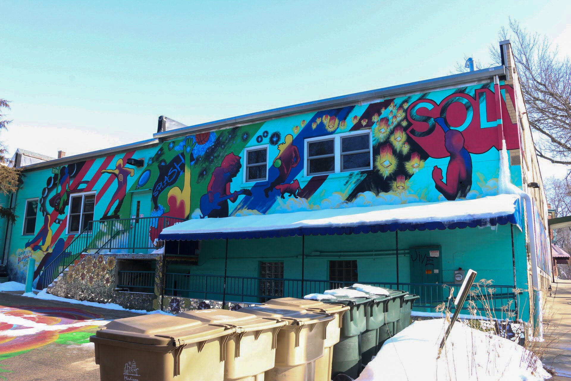 A mural on the back of the Social Justice Center building on Willy Street honors the late street artist SOLVE, a Madison native.