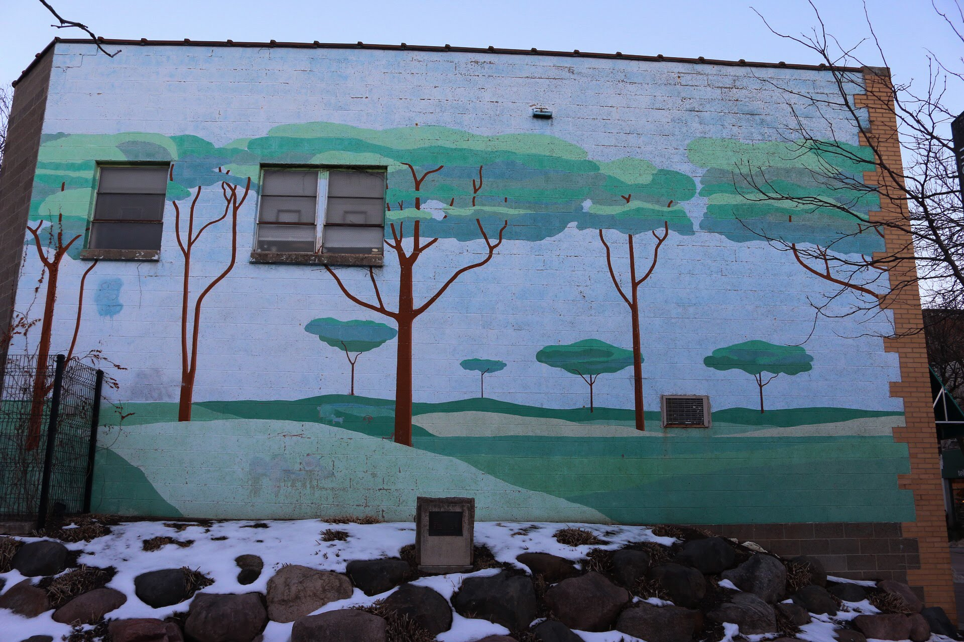 A mural of Matisse-esque trees overlooks Lisa Link Peace Park in downtown Madison.