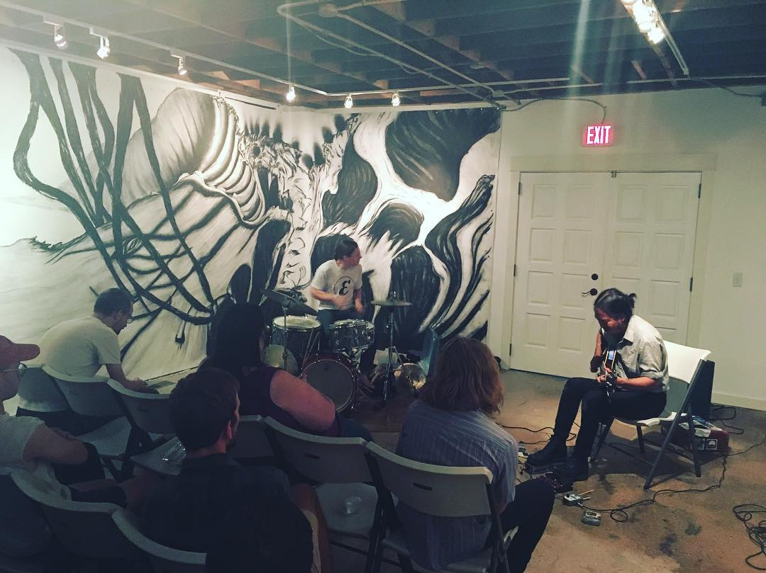 Musicians Tyler Damon (left) and Tashi Dorji playing at ALL in September 2017, in front of a mural by Brianna Lynn Hernandez Baurichter.