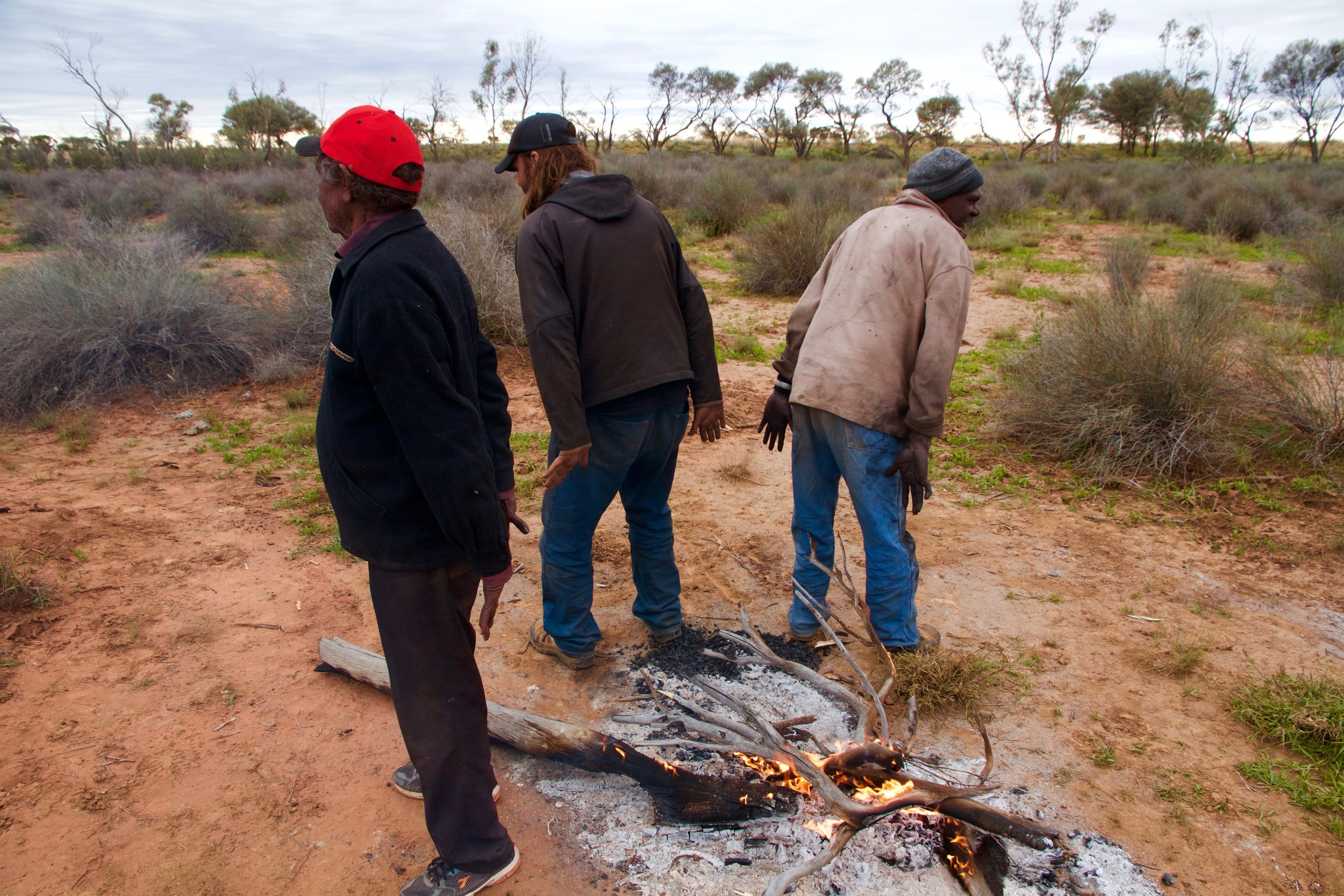 Harry Jagamarra Nelson (left), Robin Japanangka Granites (centre) and Warwick Thornton (right) by fire