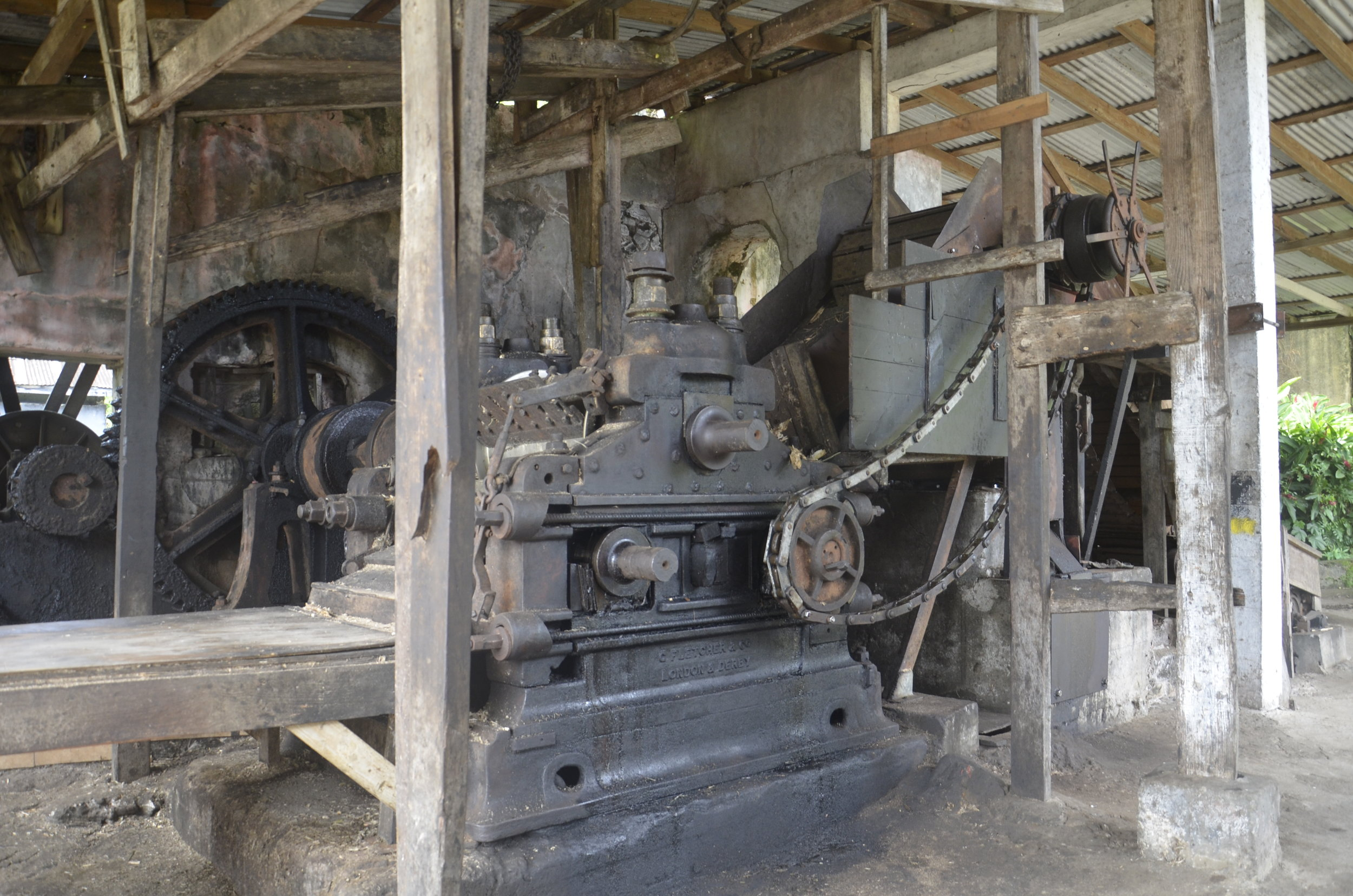 The original wooden water wheel is still used to drive this original cane pressing machine.