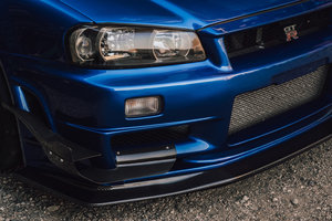 You cannot have an aggressive side but stock front end. I've chosen the Nismo Z-tune bumper fitted with Autoselect carbon canards. However, there is not a huge selection of front lip/diffuser for R34s whatsoever. It took me awhile to track down this Carshop F1 carbon front diffuser.