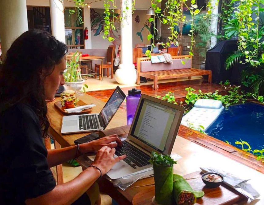 """Someone typing """"important stuff"""" while eating something unsurprisingly vegan-looking in Dojo Bali. It's all very hipster."""