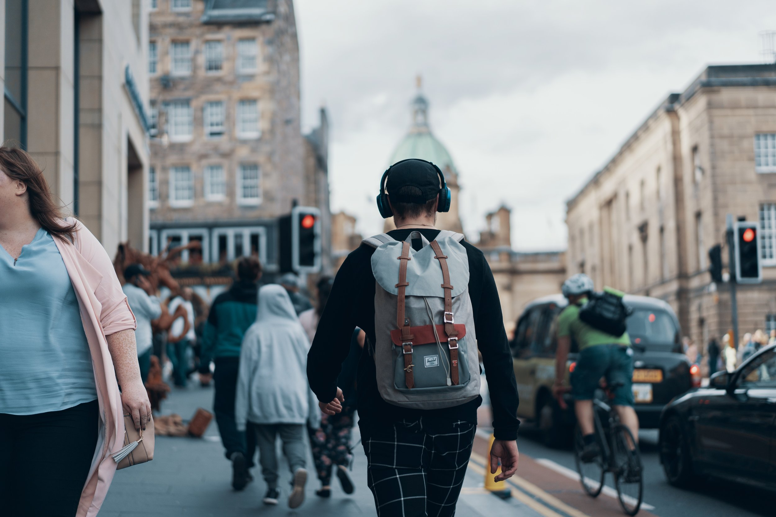 Young male with headphones walking through city streets
