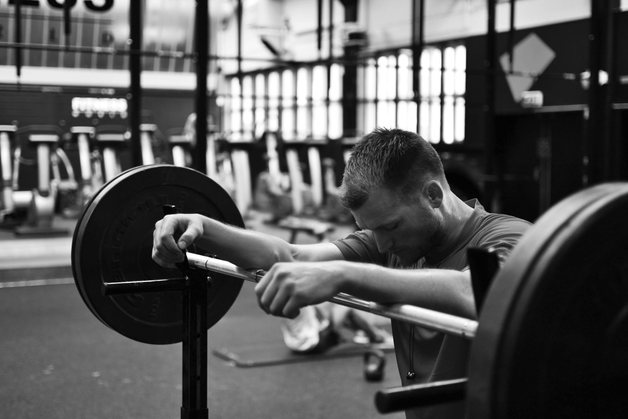 Black and white photo of young male in gym resting while doing weights