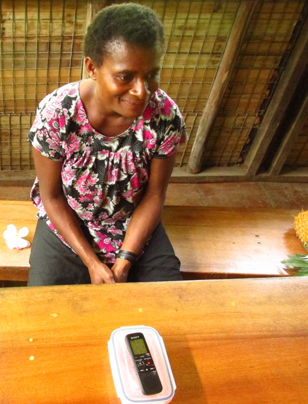 A Lusi woman sitting at a table with a voice recorder, presumably during a language learning session
