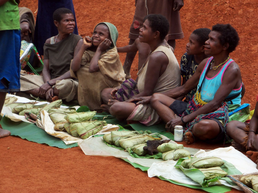 Pal women and children sitting on the ground with food in front of them