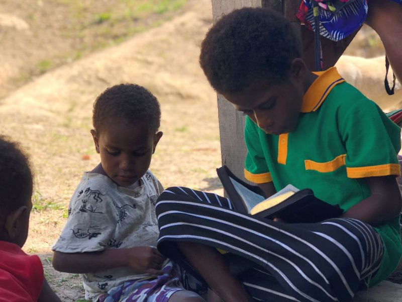 Menyan child reads the Bible as other kids sit and play
