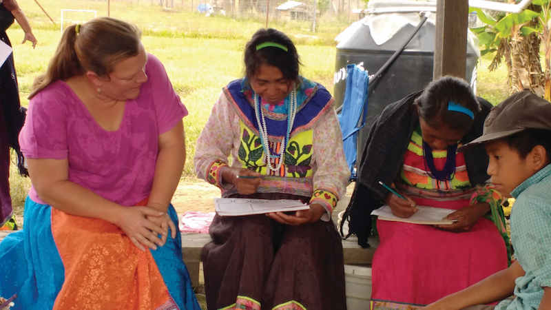 missionary helping Nahuatl people learn to read
