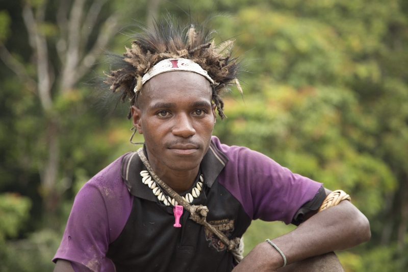 young man with traditional head dress, necklace and string bag