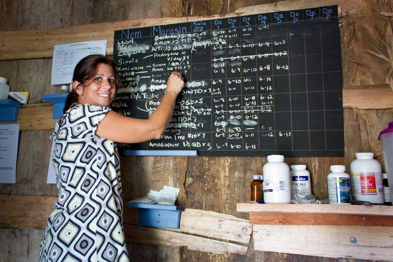 Susan Kopf writing on chalkboard in the clinic