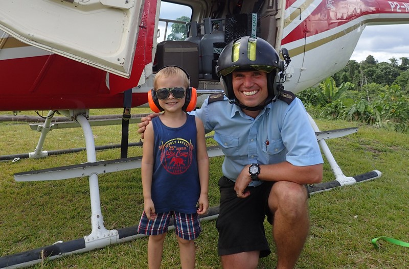 pilot and missionary kid in front of a helicopter