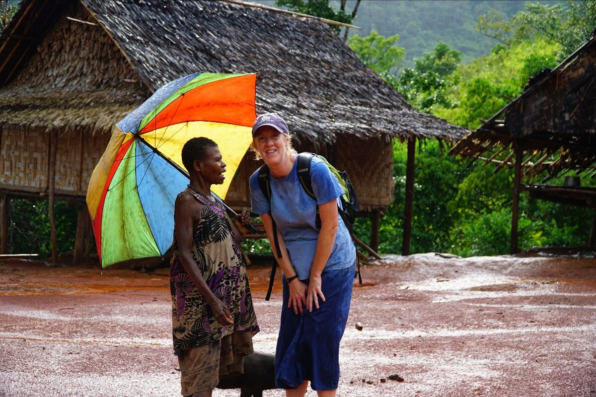 a missionary and her friend standing in the rain with an umbrella