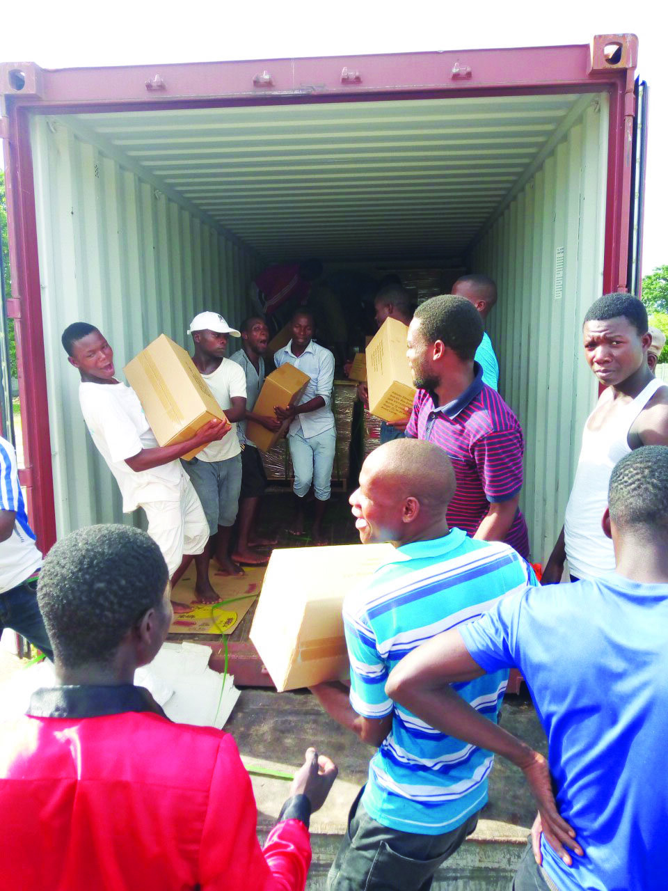 men unloading boxes of Bibles from a shipping container
